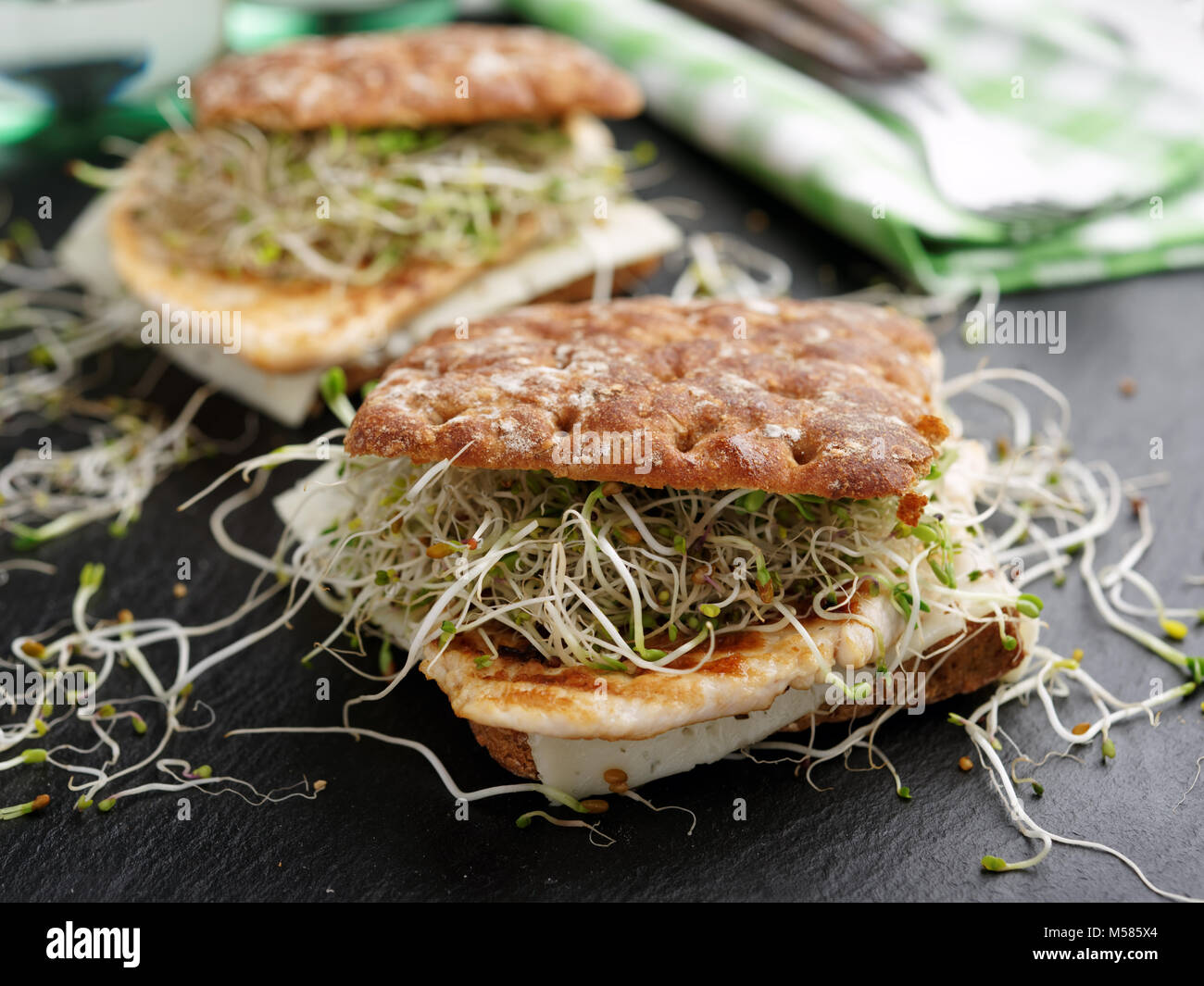 Two sandwiches with grilled turkey meat, slice of cheese, and radish sprouts on a slate cutting board - Stock Image