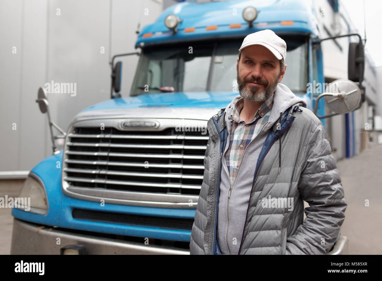 Mature bearded man against retro styled truck - Stock Image