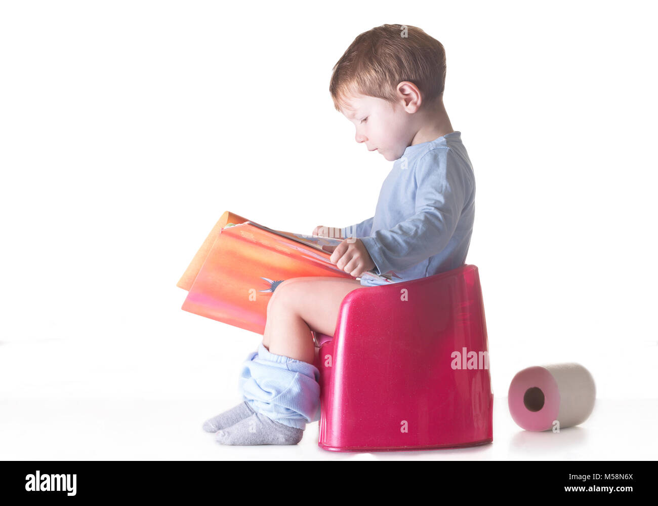 Toddler boy sitting on chamber pot reading story book. Potty training concept - Stock Image