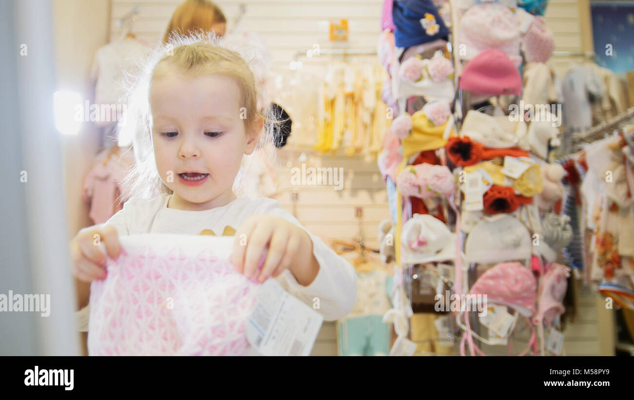 The little girl wears a pink knitted hat in shildren store - Stock Image