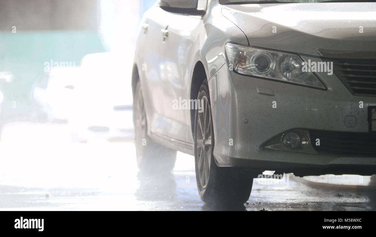 Washing a car in the suds by water hoses - Stock Image