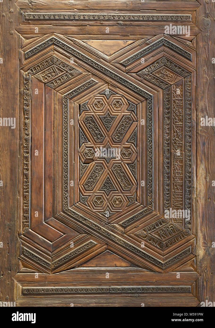 Geometrical and floral engraved patterns of Mamluk style wooden ornate door leaf of Madrasa of Sultan Nagm al Din - Stock Image