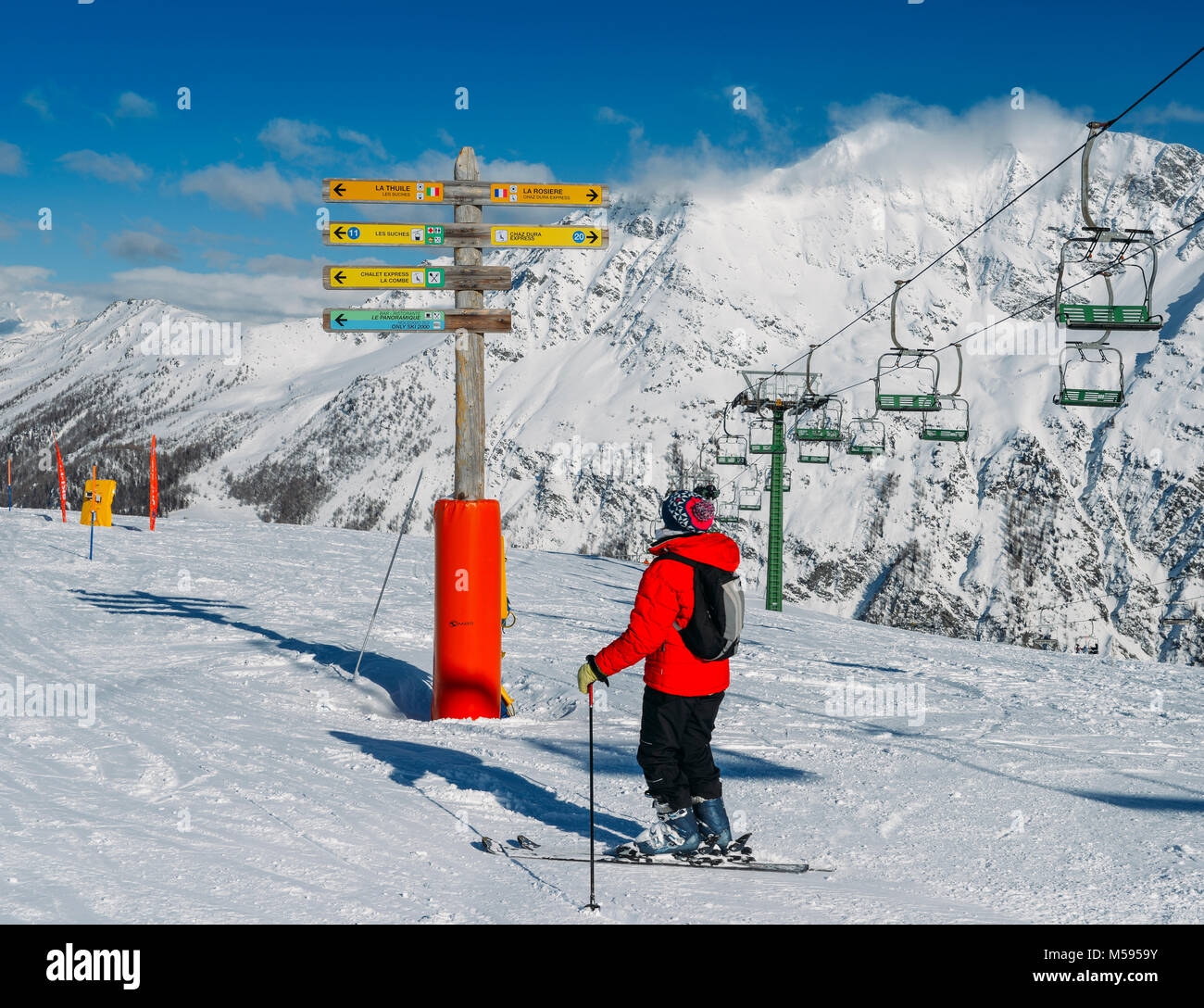 skier-looking-at-signpost-in-the-ski-resort-of-la-thuile-pointing-M5959Y.jpg