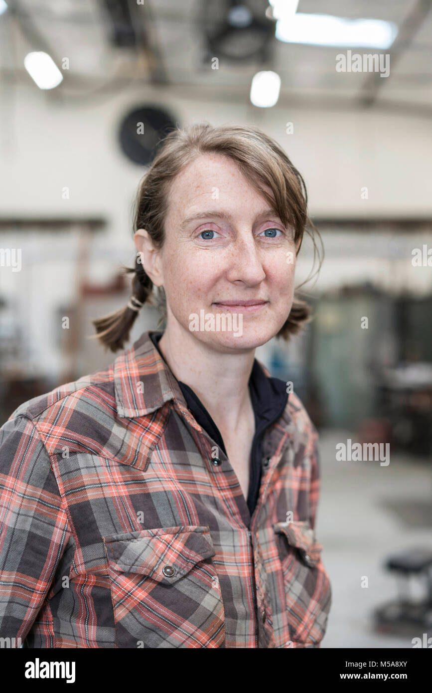 Blond woman wearing checkered shirt standing in metal workshop, smiling at camera. - Stock Image