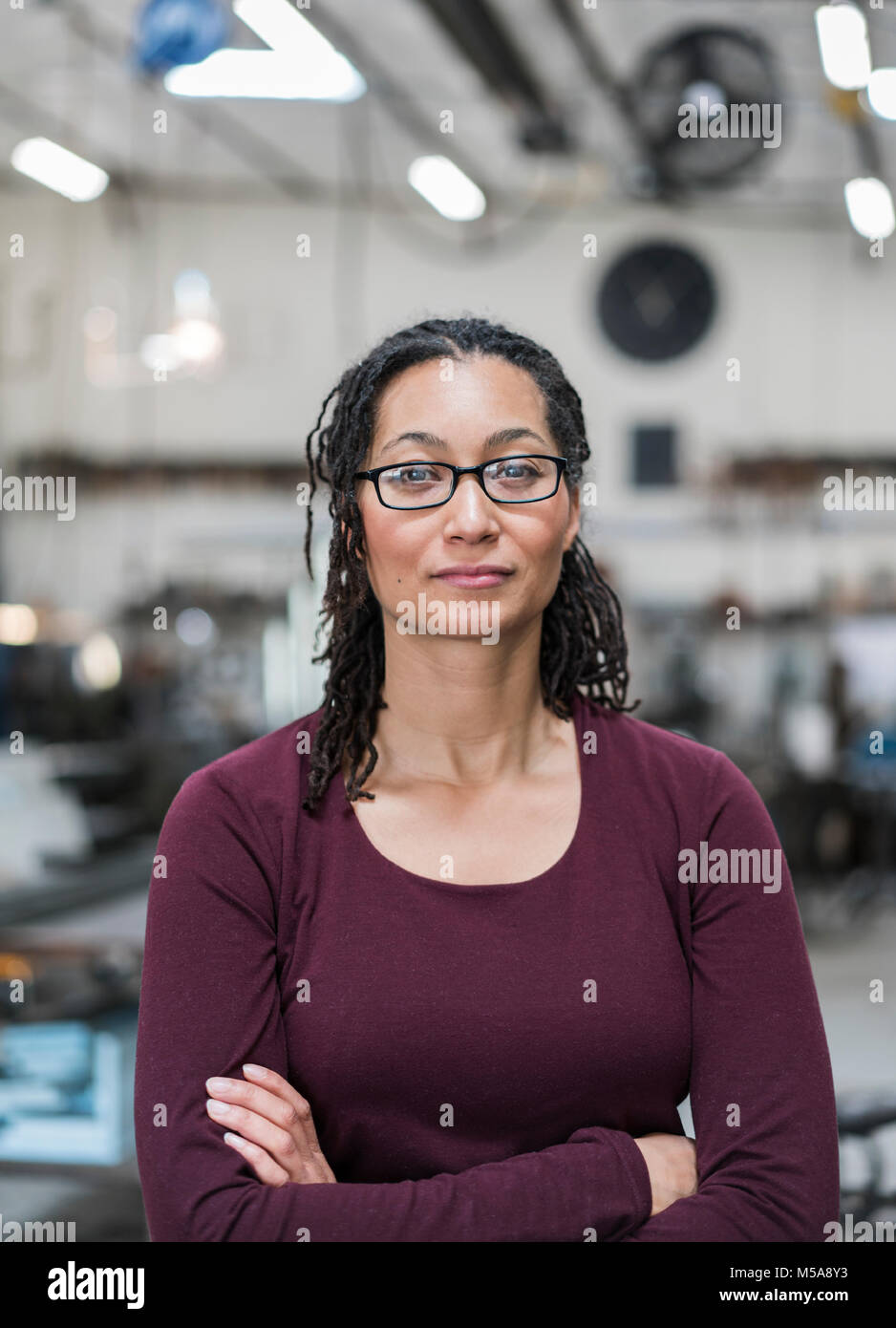 Woman with brown hair wearing glasses standing in metal workshop, smiling at camera. - Stock Image