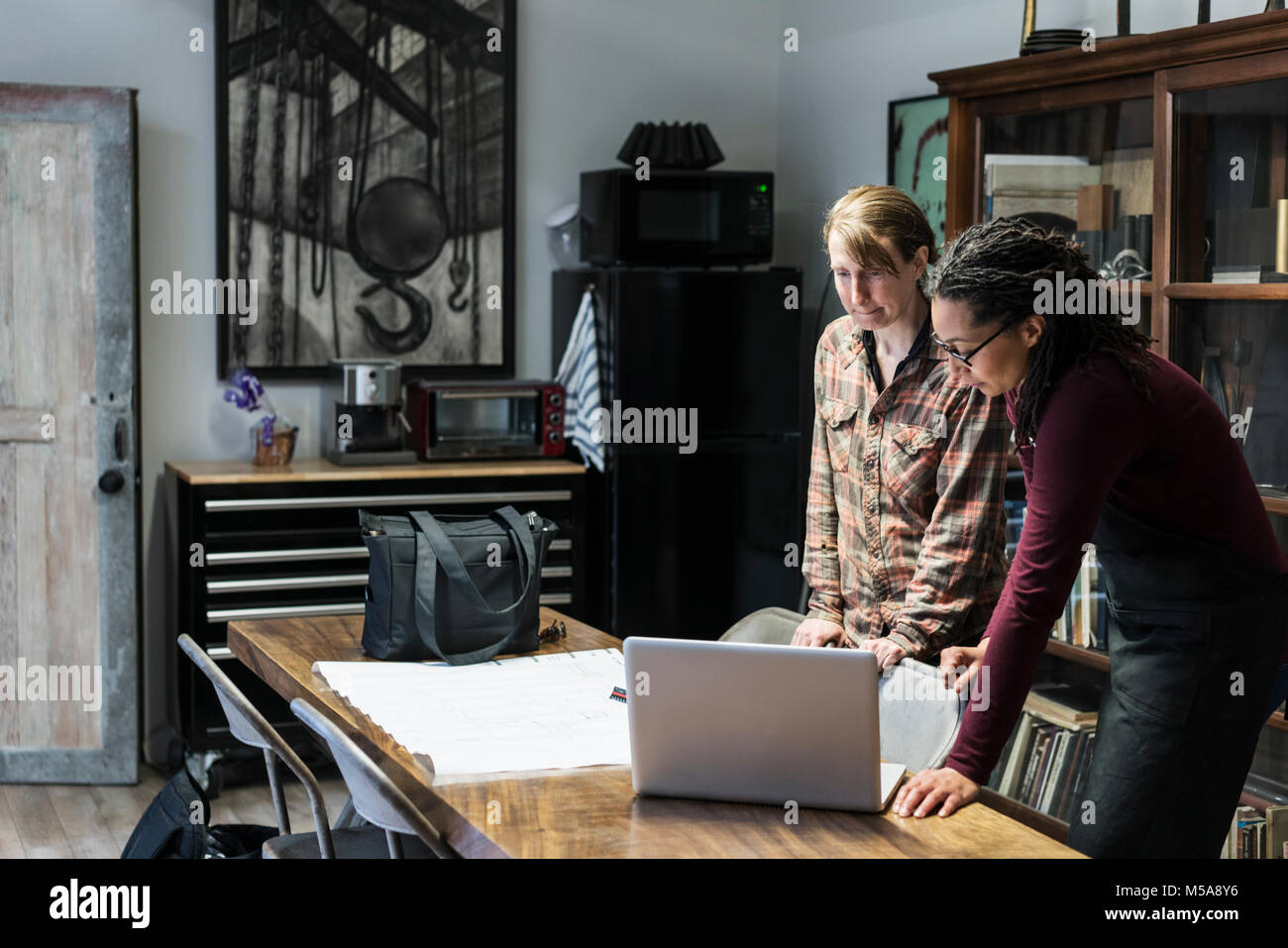 Two women gathered around table in office area of a metal workshop, looking at laptop. - Stock Image