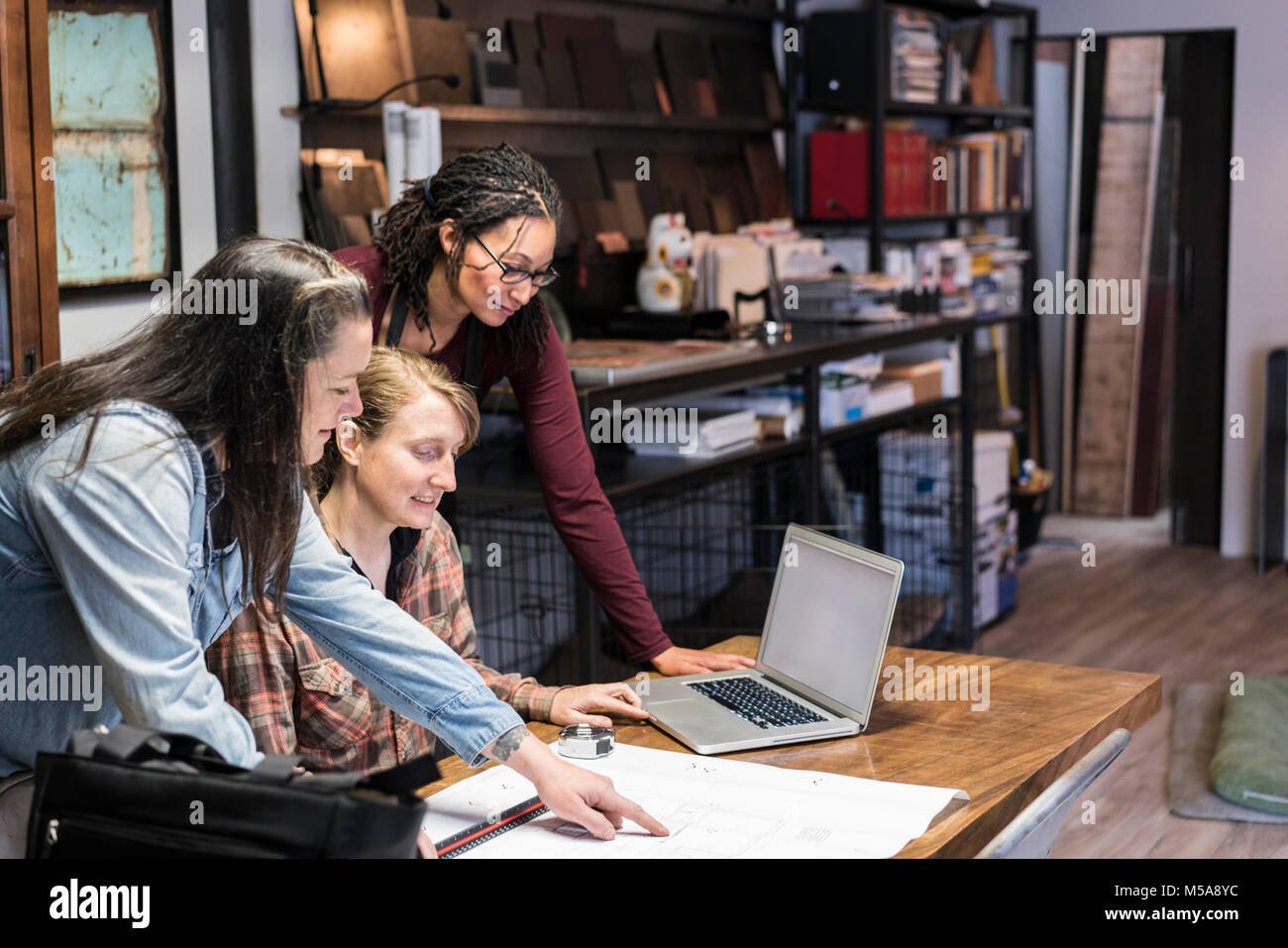 Three women gathered around table in office area of a metal workshop. - Stock Image