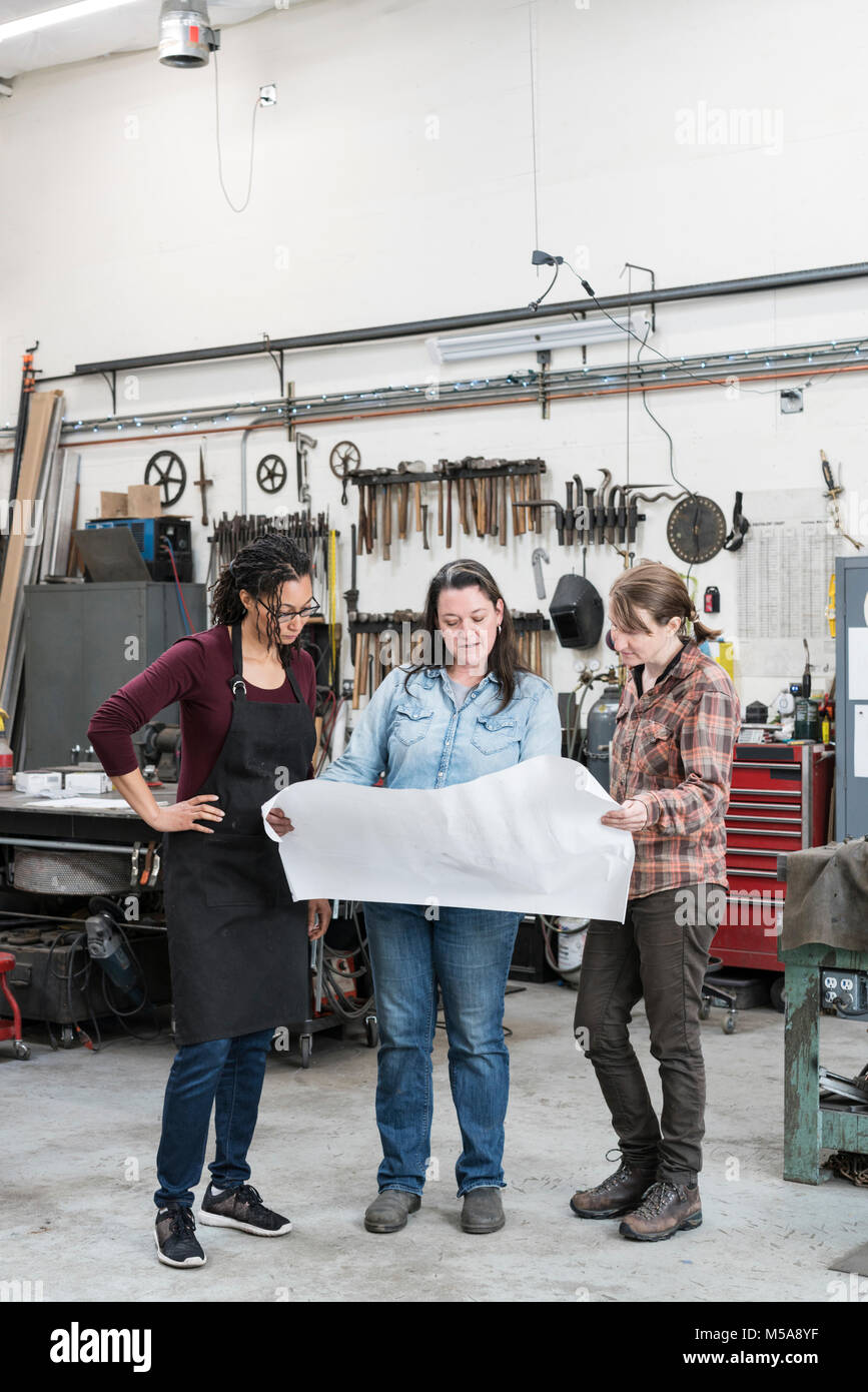 Three women standing in metal workshop, holding technical blueprint. - Stock Image