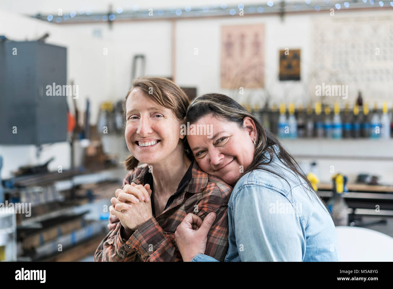 Two women standing in metal workshop, hugging and smiling at camera. - Stock Image
