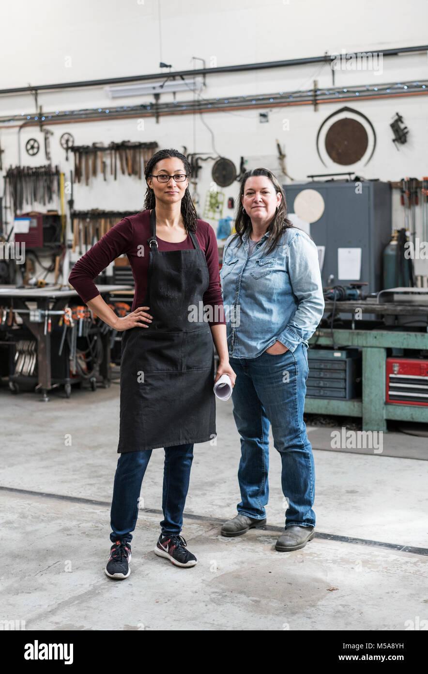Two women wearing apron and Denim shirt standing in metal workshop, smiling at camera. - Stock Image