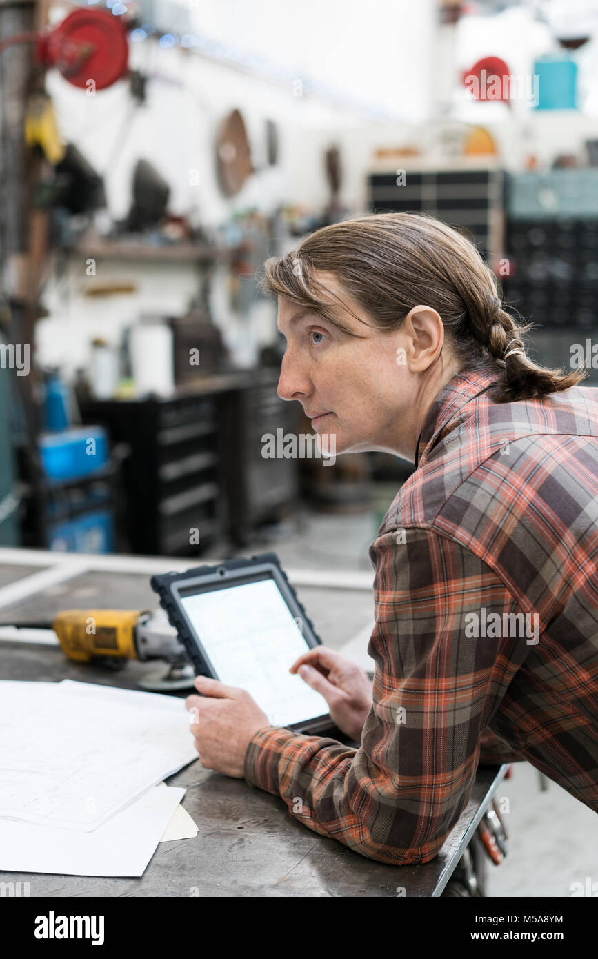 Side view of blond woman wearing checkered shirt standing at workbench in metal workshop, holding digital tablet. - Stock Image