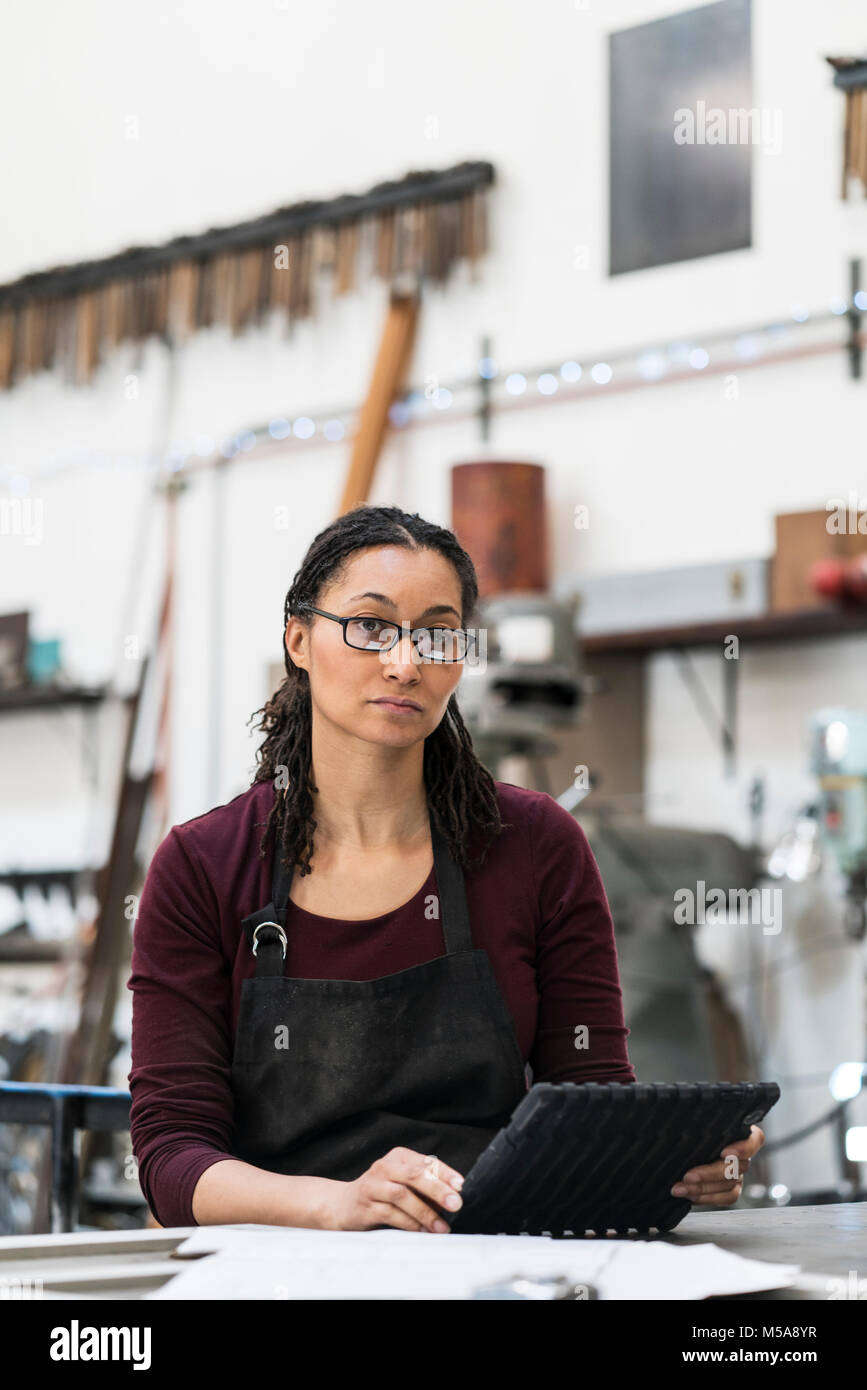 Woman wearing glasses and apron standing at workbench in metal workshop, holding digital tablet, looking at camera. - Stock Image