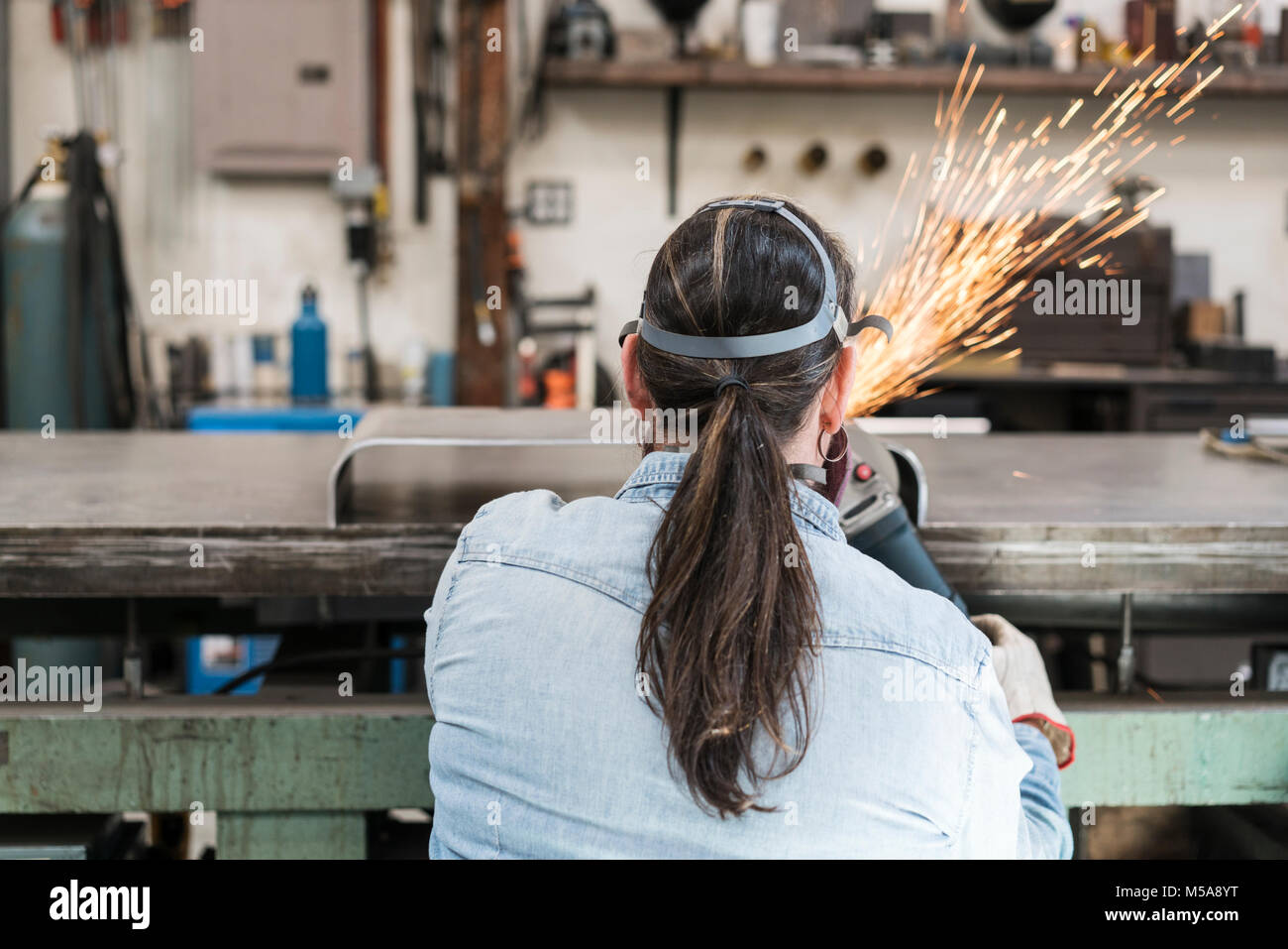Rear view of woman wearing safety glasses and dust mask standing in metal workshop, using power grinder, sparks - Stock Image
