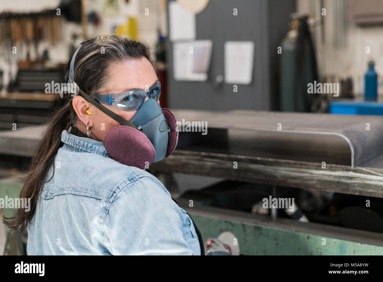 Woman wearing safety glasses and dust mask standing in metal workshop, looking at camera. - Stock Image
