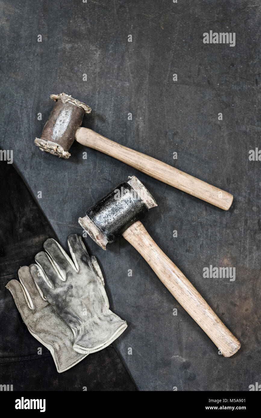 High angle close up of two hammers and pair of leather safety gloves in a metal workshop. - Stock Image