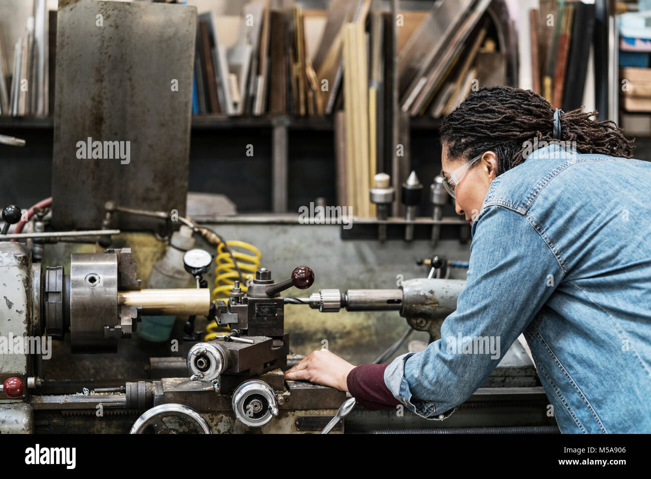 Woman wearing safety glasses standing in a metal workshop, working at a machine. - Stock Image