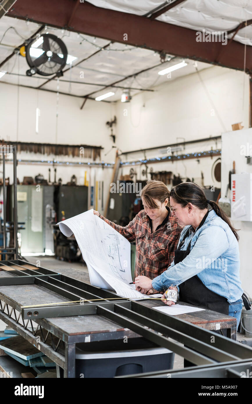 Two women standing at workbench in a metal workshop, looking at technical blueprint. - Stock Image