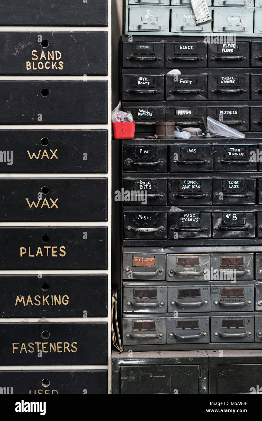 Close up of stack of metal drawers containing selection of hardware for metal work. - Stock Image