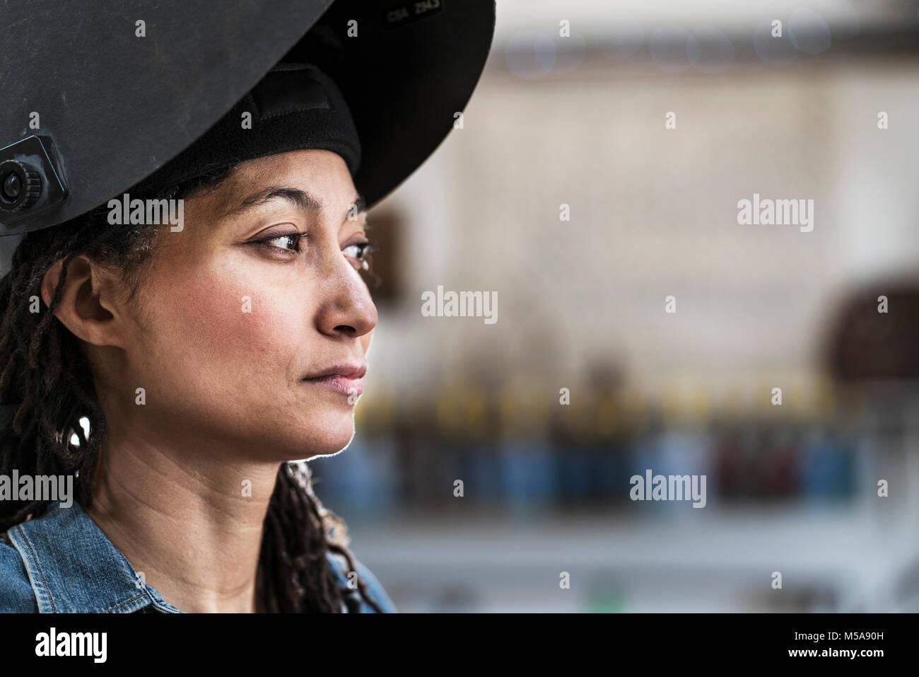 Portrait of woman wearing welding mask standing in metal workshop. - Stock Image