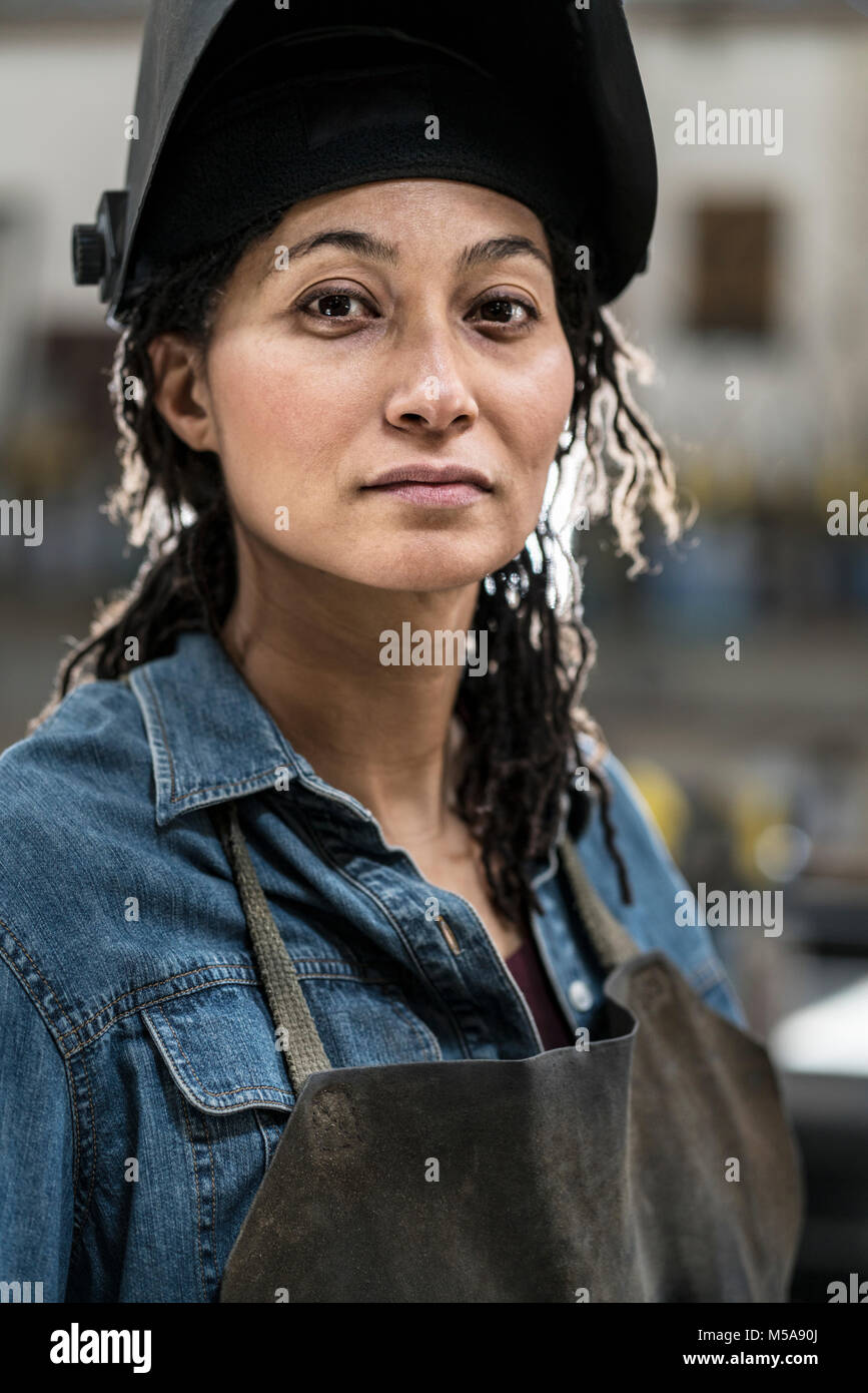 Portrait of woman wearing apron and welding mask standing in metal workshop, smiling at camera. - Stock Image