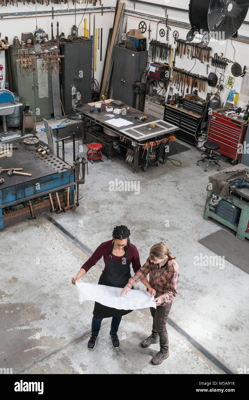 High angle view of two women standing in metal workshop, holding technical blueprint. - Stock Image