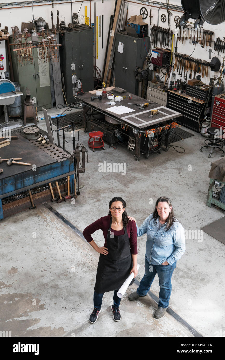 High angle view of two women standing in metal workshop, looking at camera. - Stock Image