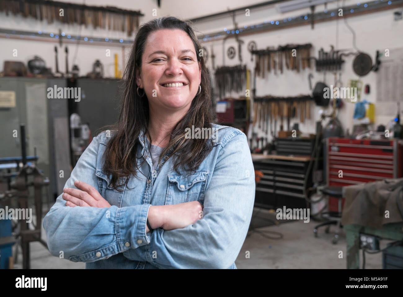 Woman with brown hair wearing Denim shirt standing in metal workshop, smiling at camera. - Stock Image