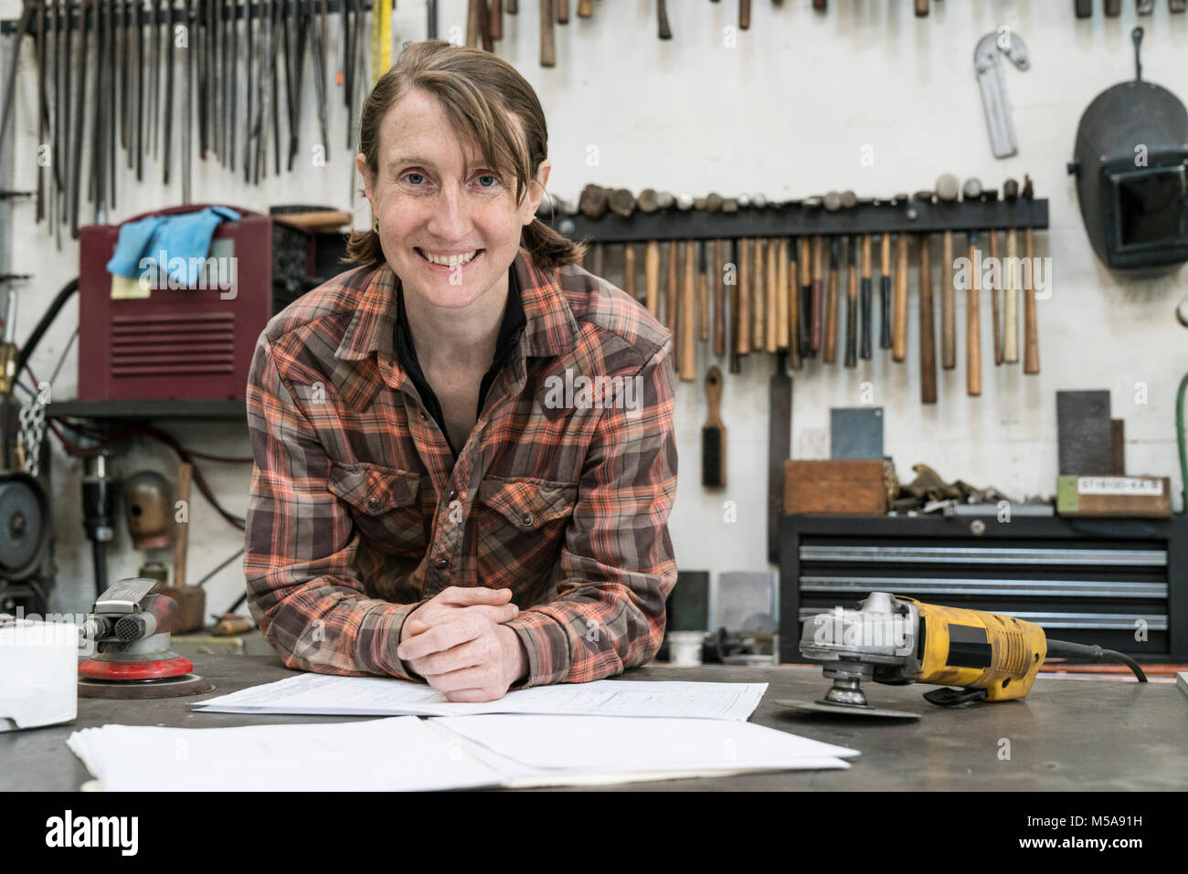 Blond woman wearing checkered shirt standing in metal workshop, looking at camera. - Stock Image