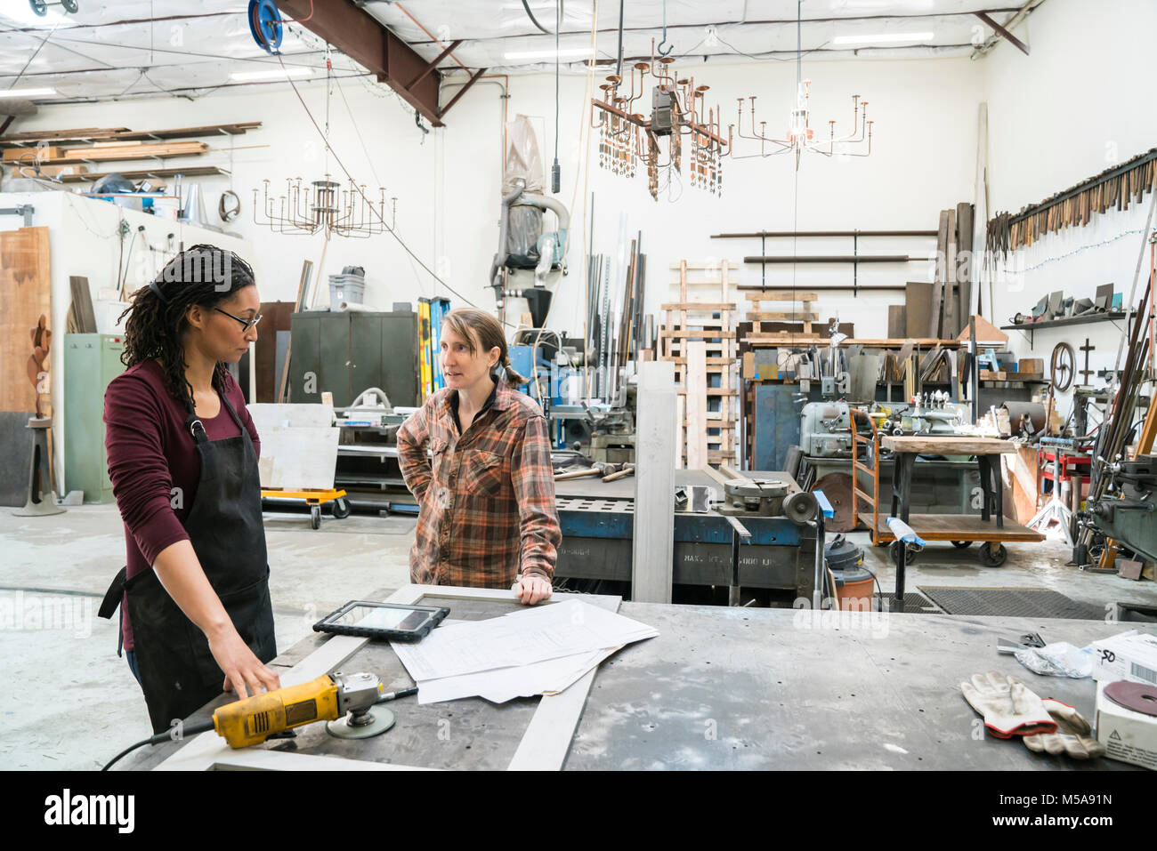 Two women standing at workbench in metal workshop. - Stock Image