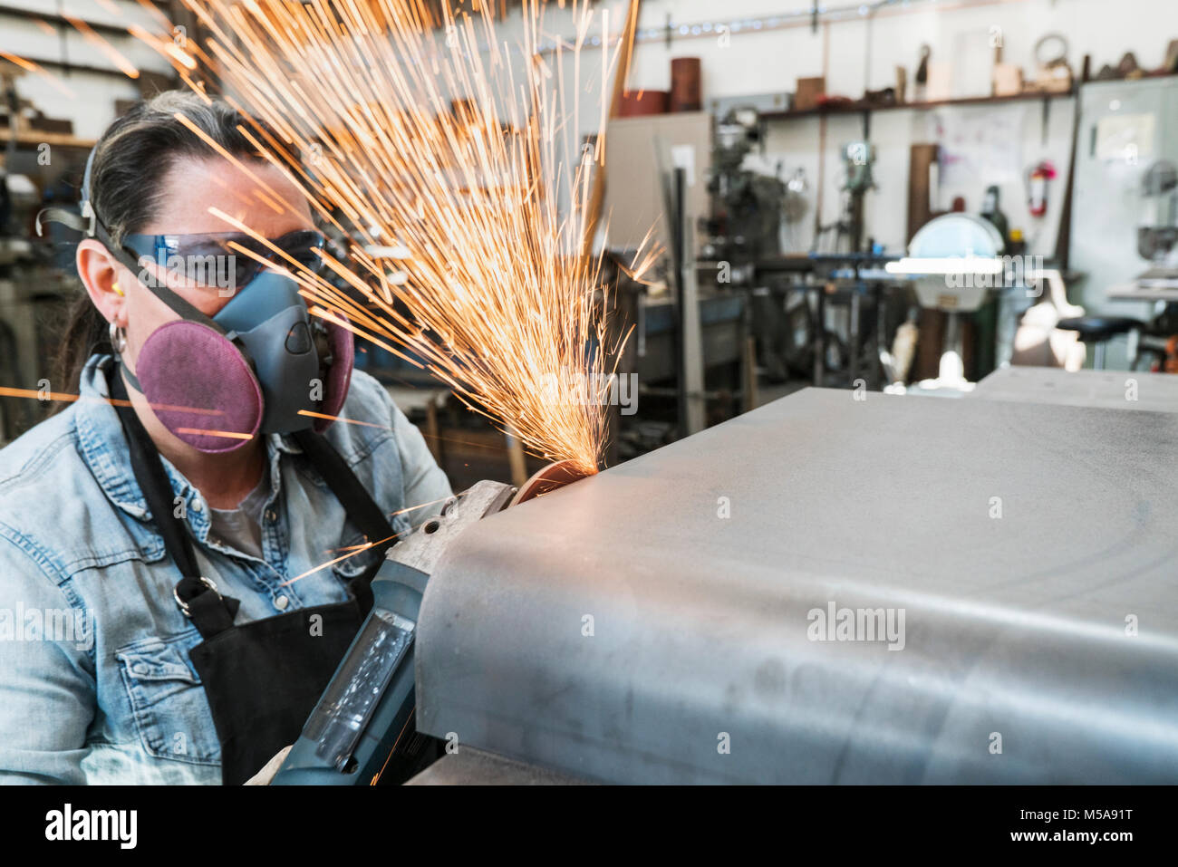 Woman wearing safety glasses and dust mask standing in metal workshop, using power grinder, sparks flying. - Stock Image