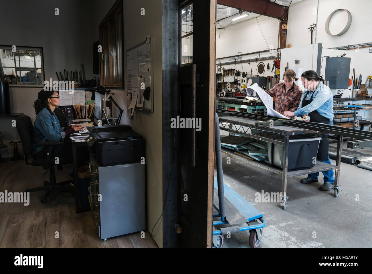 Two women at a desk in office area of a metal workshop, woman standing at mobile workbench. - Stock Image