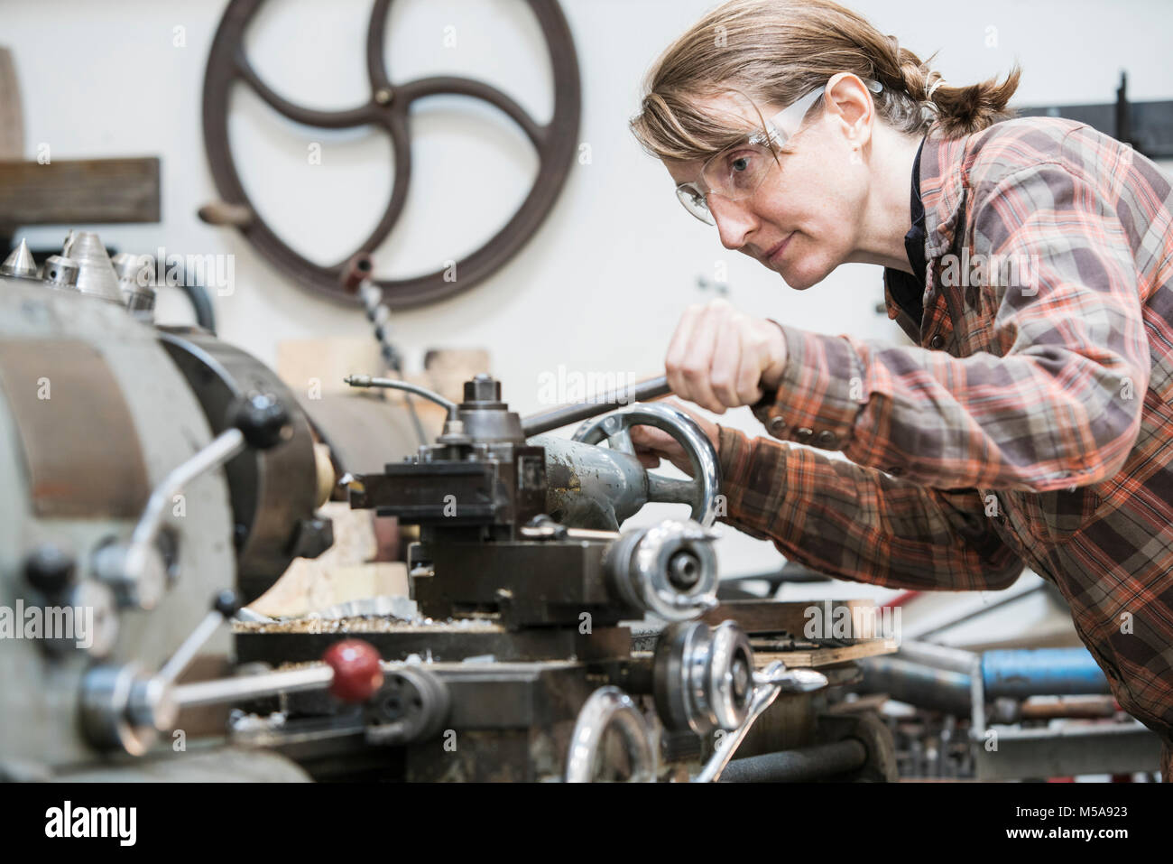 Woman wearing safety glasses standing in a metal workshop, working at metal lathe machine. - Stock Image