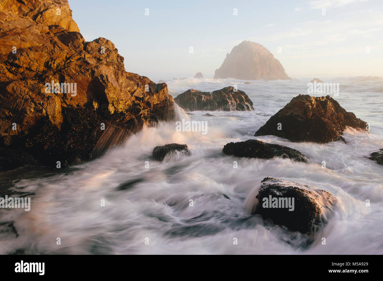 Seascape with breaking waves over rocks at dusk. - Stock Image