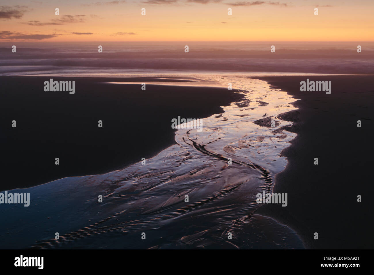 Landscape with stream flowing into ocean surf at dusk. - Stock Image