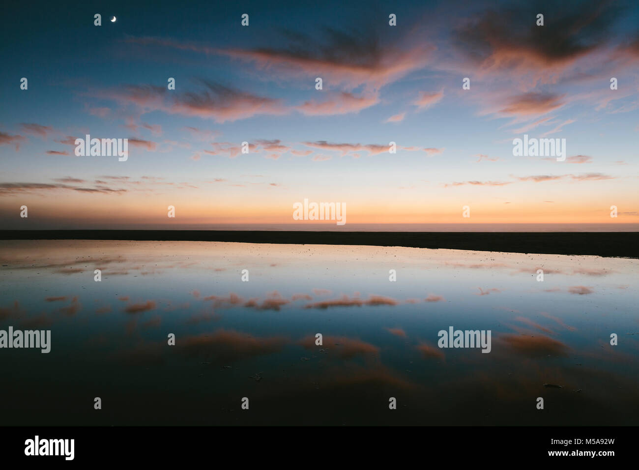 Seascape with dramatic sky reflected in water at dusk. - Stock Image