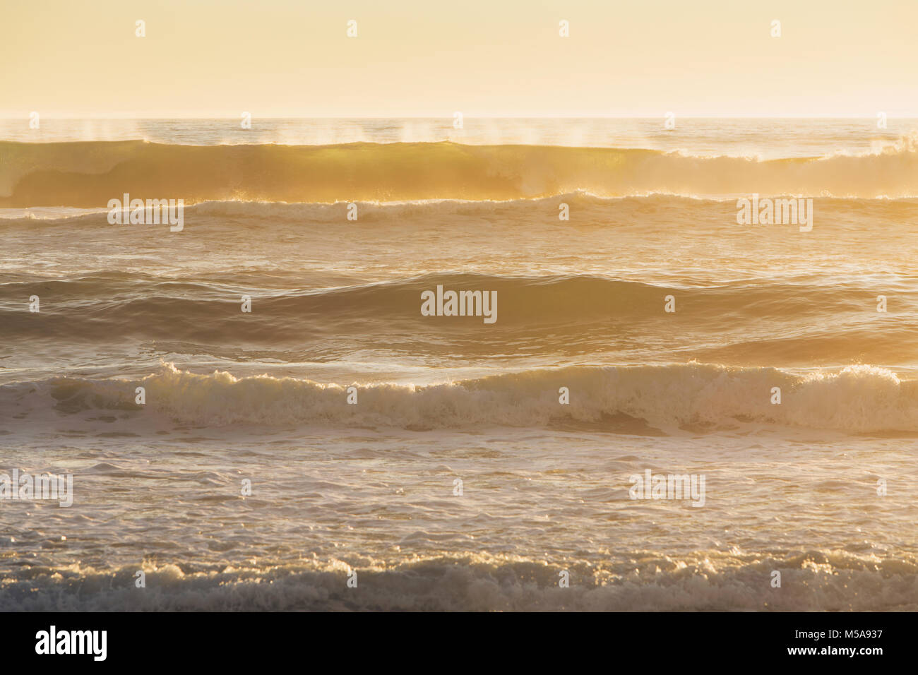 Seascape with breaking waves under cloudy sky at sunset. - Stock Image