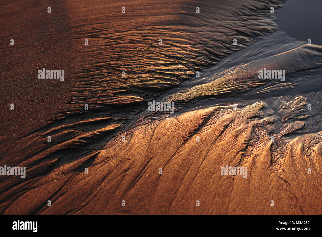High angle close up of patterns in beach sand at dusk. - Stock Image