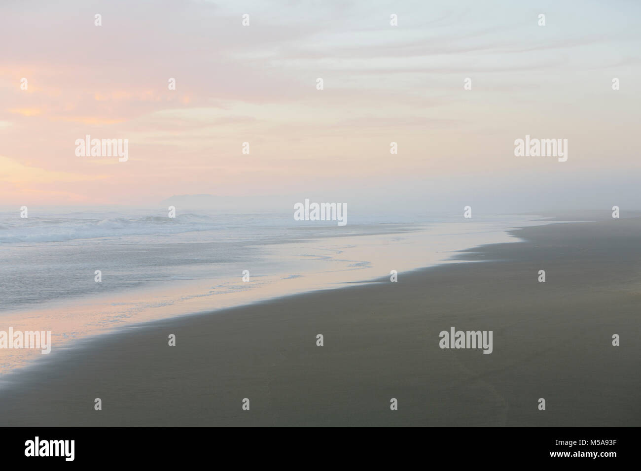 Landscape with sandy beach and ocean at sunset. - Stock Image