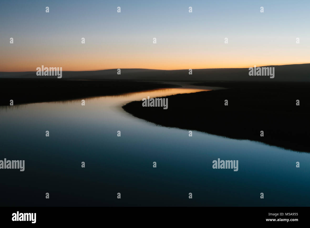 The open spaces of marshland and water channels. Flat calm water.  Dusk. - Stock Image