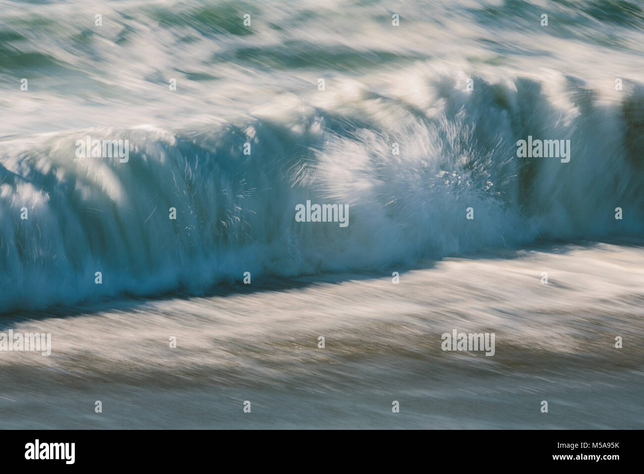Waves crashing and breaking on the shore. - Stock Image