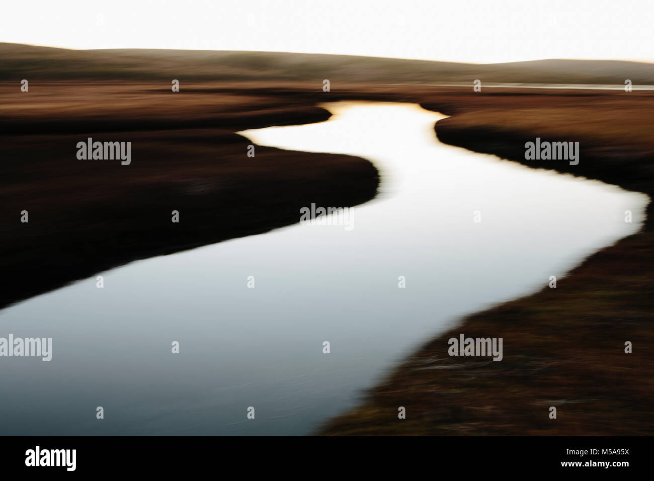 The open spaces of marshland and water channels. Flat calm water. - Stock Image