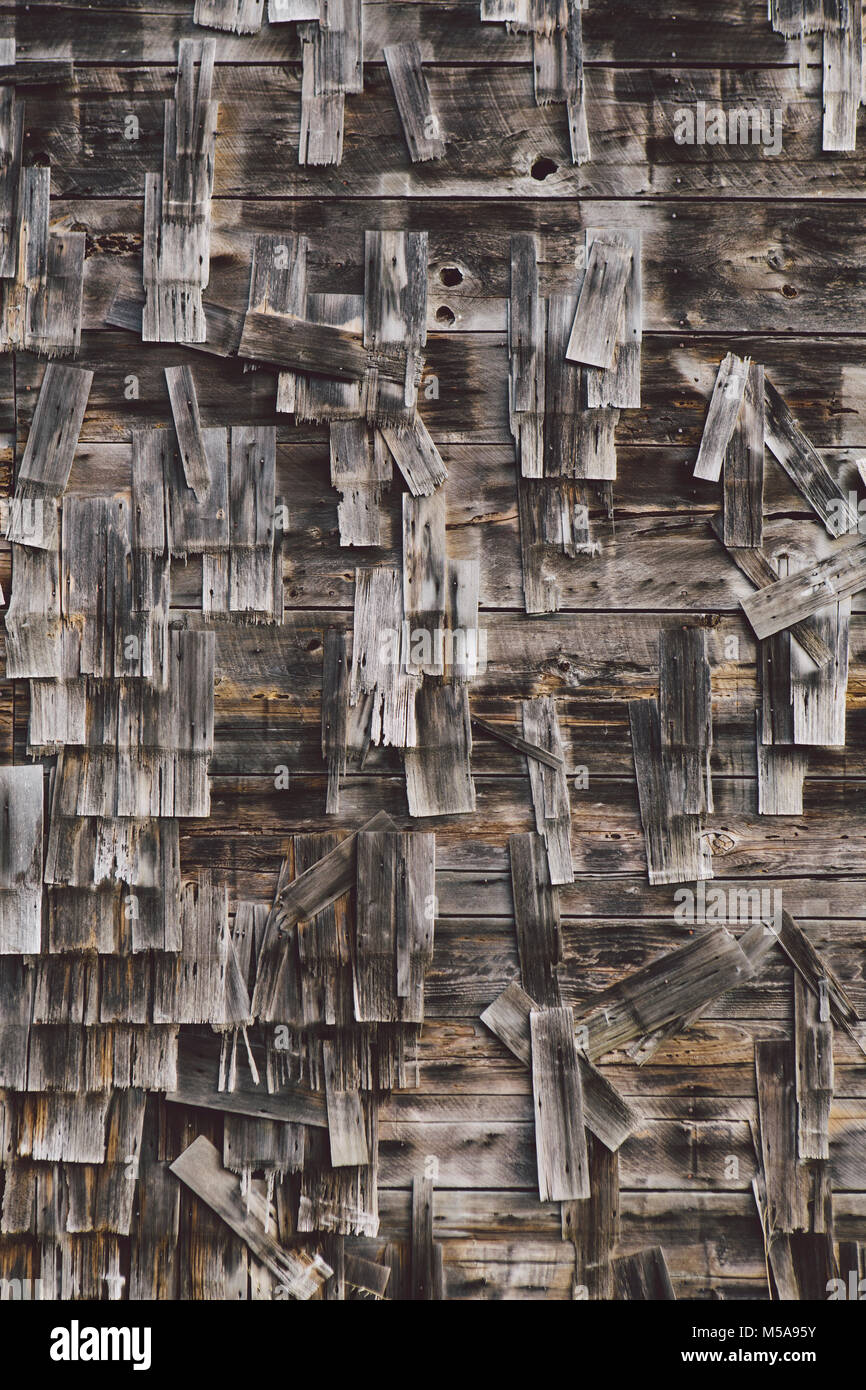 An old farmhouse with wooden shingle tiles on the walls. Silvery grey colours. - Stock Image
