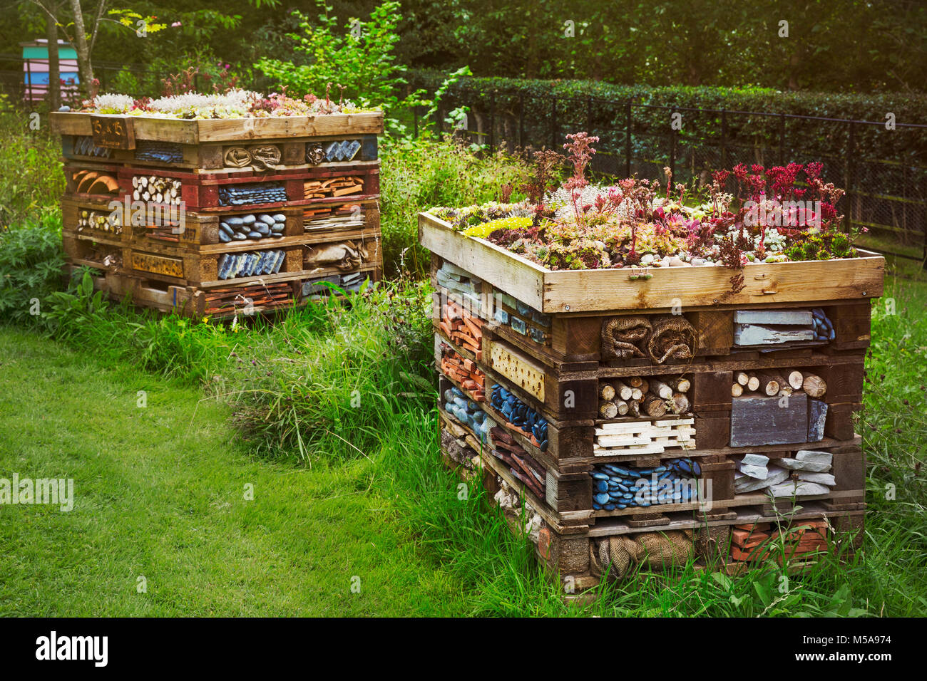 Two large bug houses with several layers of different materials in a garden. - Stock Image