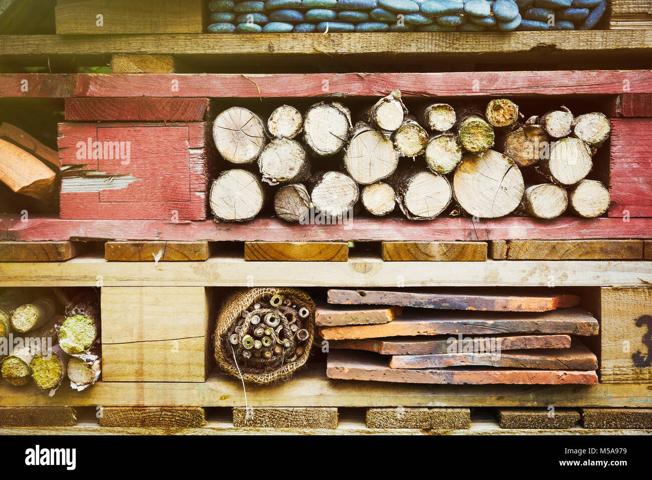 Close up of large bug house with several layers of different materials. - Stock Image