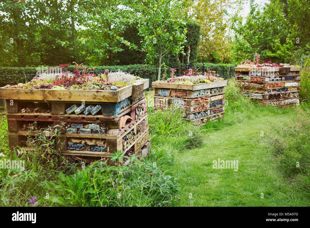 Three large bug houses with several layers of different materials in a garden. - Stock Image