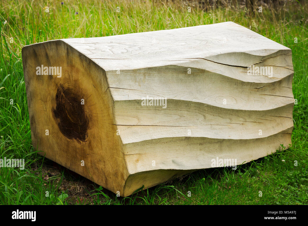 Close up of carved piece of tree trunk with wave pattern lying on grass. - Stock Image