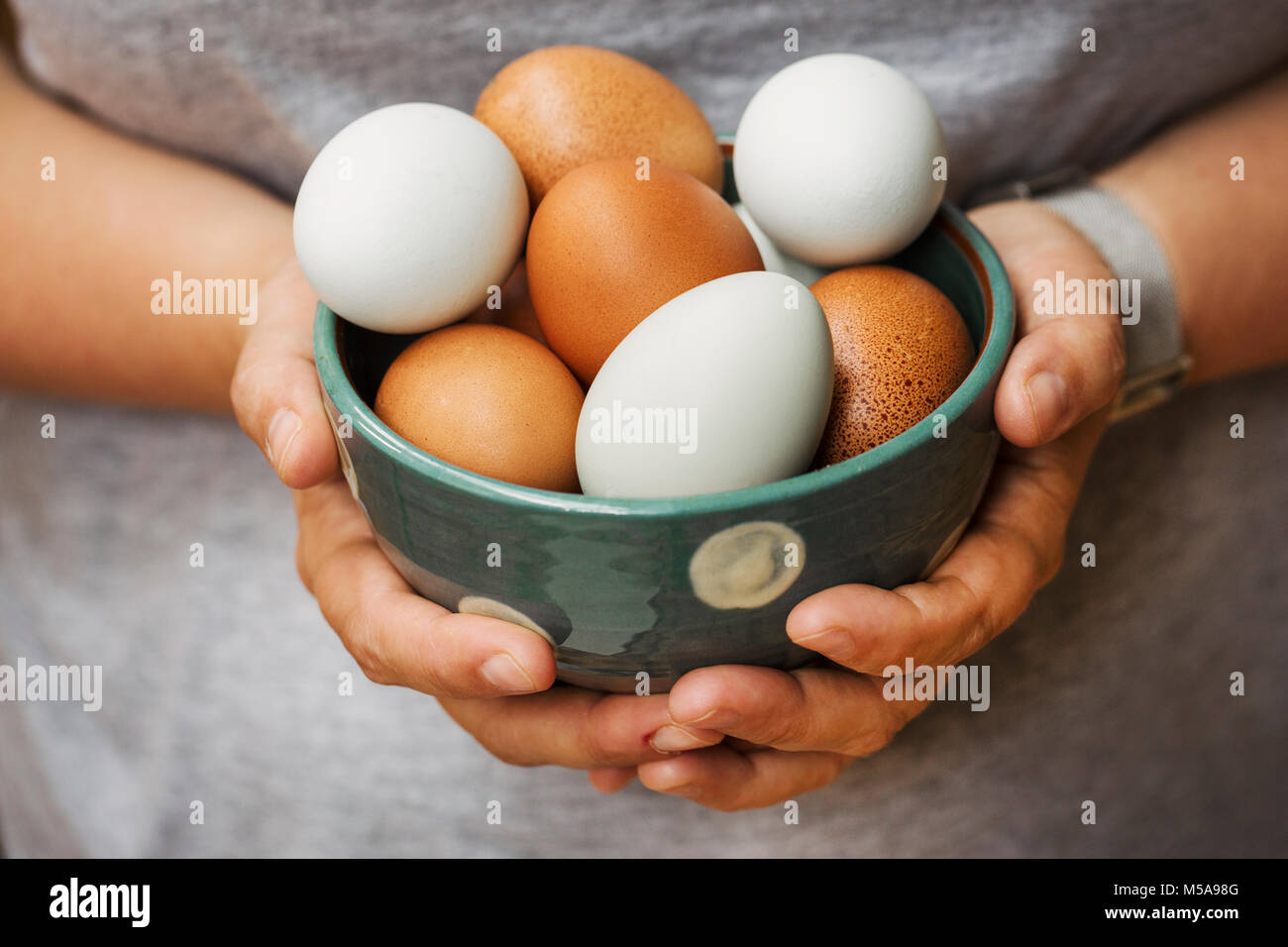 A woman holding bowl with fresh brown and white eggs. - Stock Image
