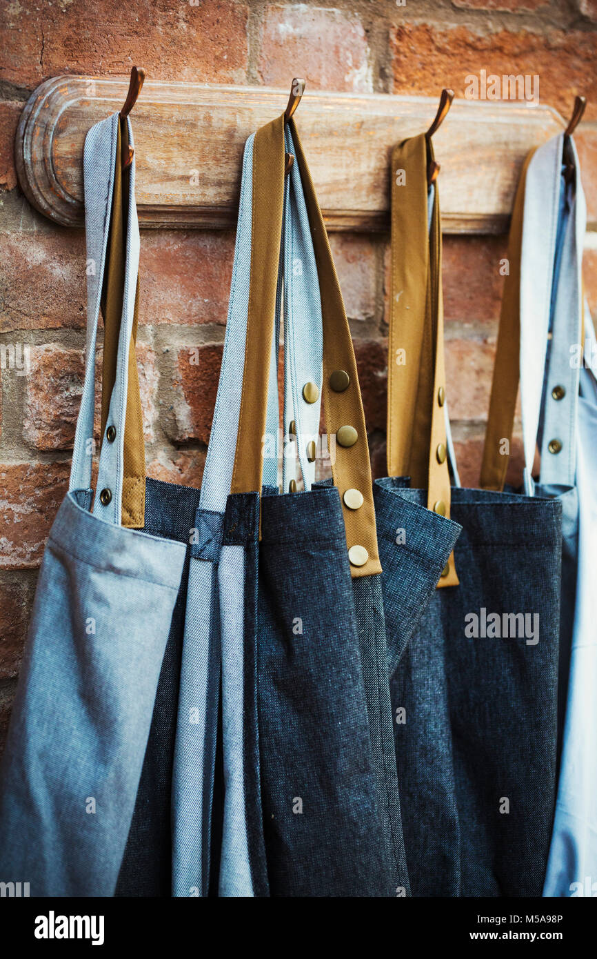 Denim work aprons hanging on a row of hooks on a brick wall. - Stock Image