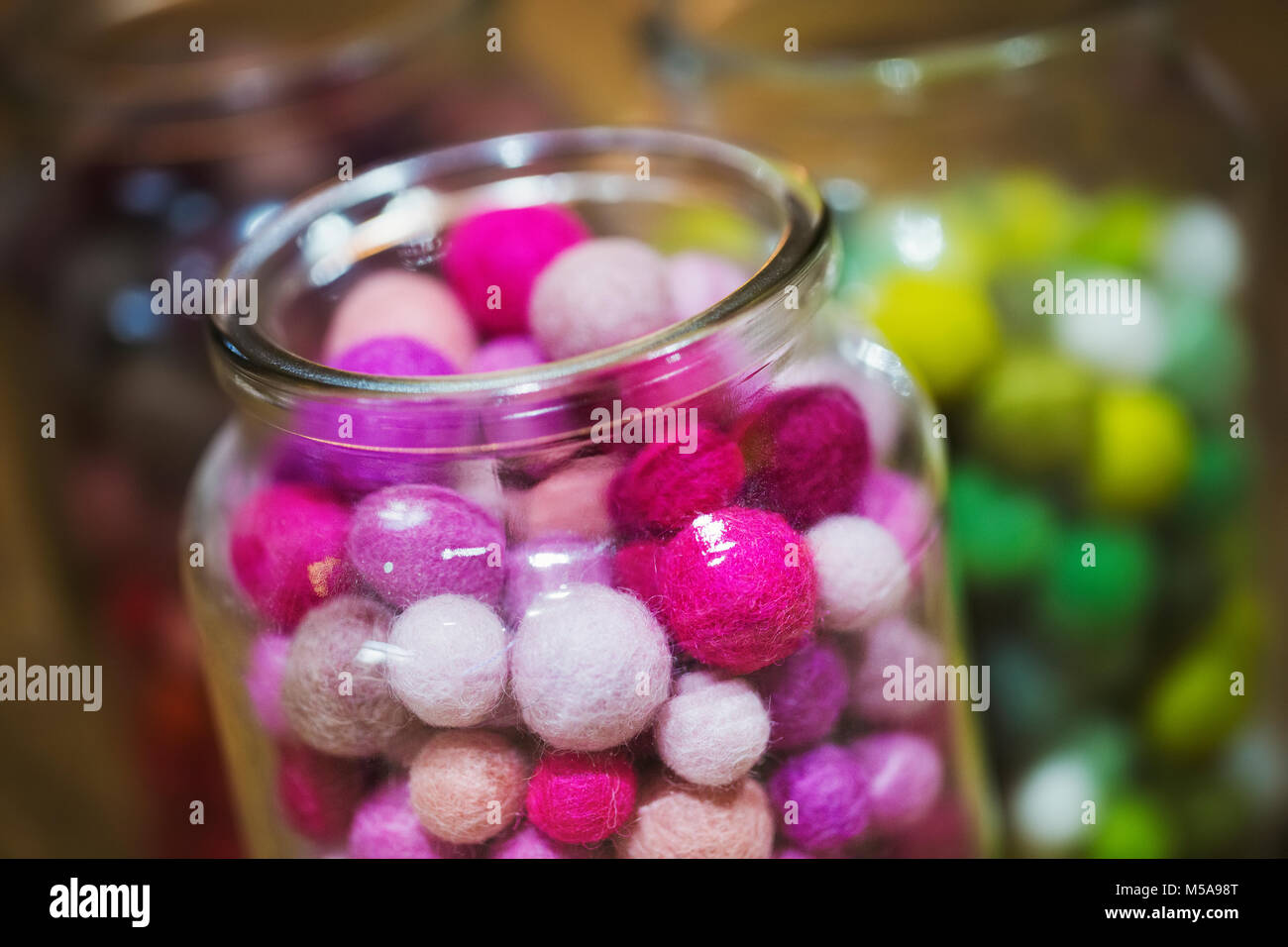 Close up of glass jars with selection of colourful small fabric balls. - Stock Image