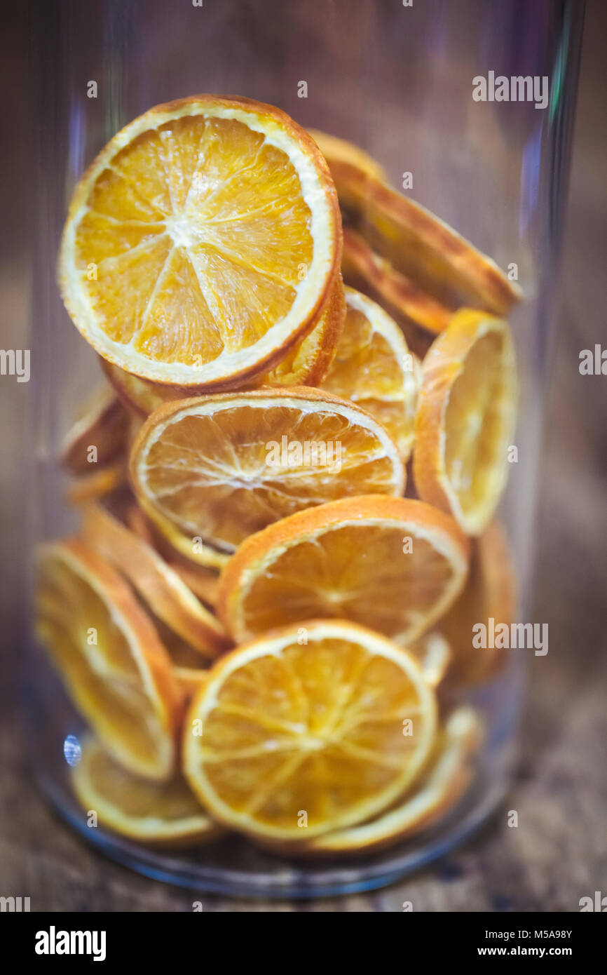 High angle close up of glass with slices of dried oranges. - Stock Image